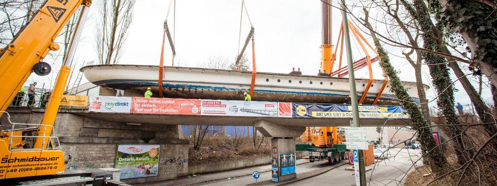 Tonnenschwerer Kran hebt die MS Utting auf die Eisenbahnbrücke