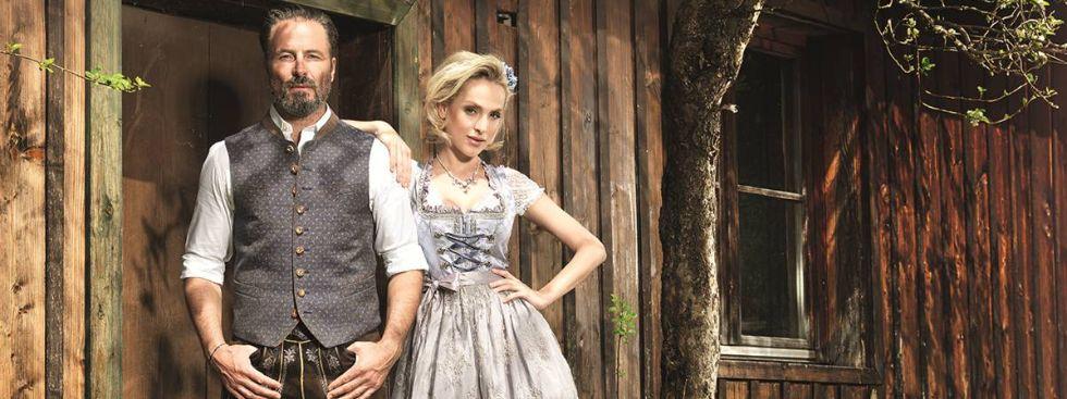 Paar steht in Tracht vor einem Holzhaus