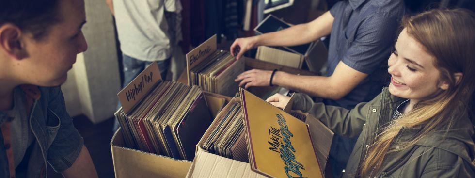 Junge Frau kauft Schallplatte auf Flohmarkt