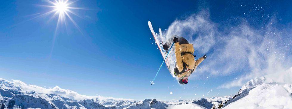 Skifahrer trickst vor Bergpanorama