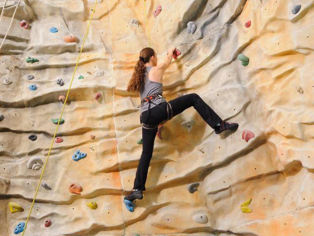Frau an Kletterwand, Foto: Sorbis/Shutterstock.com