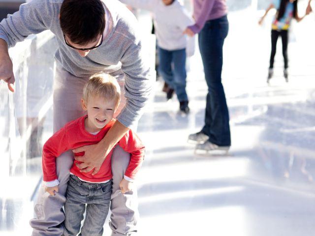 Vater mit Sohn beim Eislaufen