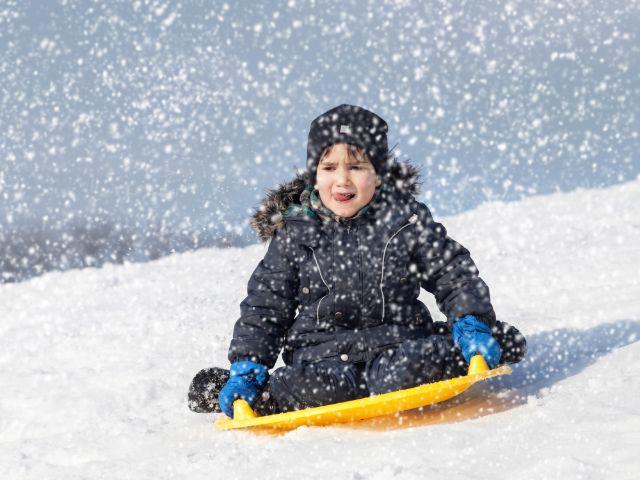 Kind rodelt durch den fallenden Schnee, Foto: Mykhaylo Palinchak / Shutterstock.com