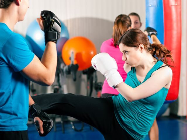 Frau trainiert Kickboxen im Sportstudio, Foto: Kzenon / Shutterstock.com