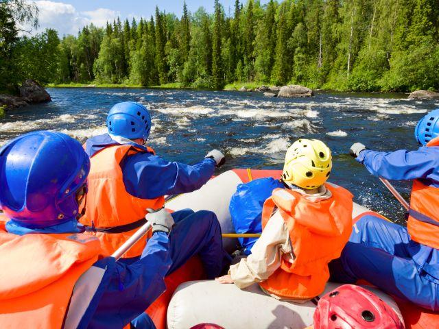 Gruppe junger Leute beim Wildwasser-Rafting auf idyllischem Fluss, Foto: Dmitry Naumov / Shutterstock.com