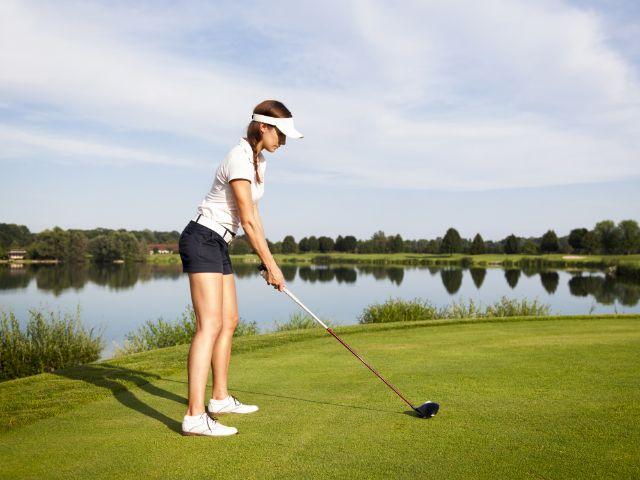 Frau bringt sich auf dem Golfplatz für den Abschlag in Stellung., Foto: Lichtmeister / Shutterstock