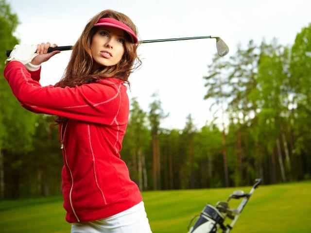 Frau auf dem Golfplatz holt mit ihrem Schläger aus., Foto: Zoom Team / Shutterstock