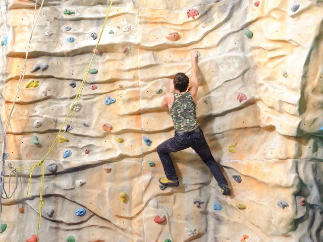 Mann in Tanktop erklimmt Kletterwand