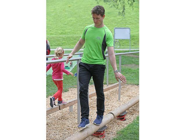 Mann balanciert auf Holzstamm, Foto: AOK Bayern