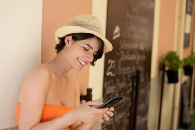 Frau mit Smartphone in Straßencafé