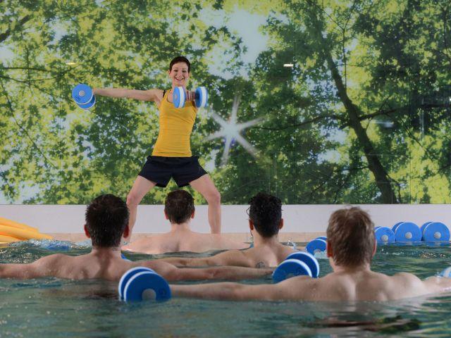 Frau animiert Männer beim Aquafitness