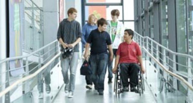 Schüler, darunter einer im Rollstuhl, in einem barrierefreien Gebäudegang, Foto: Pfennigparade