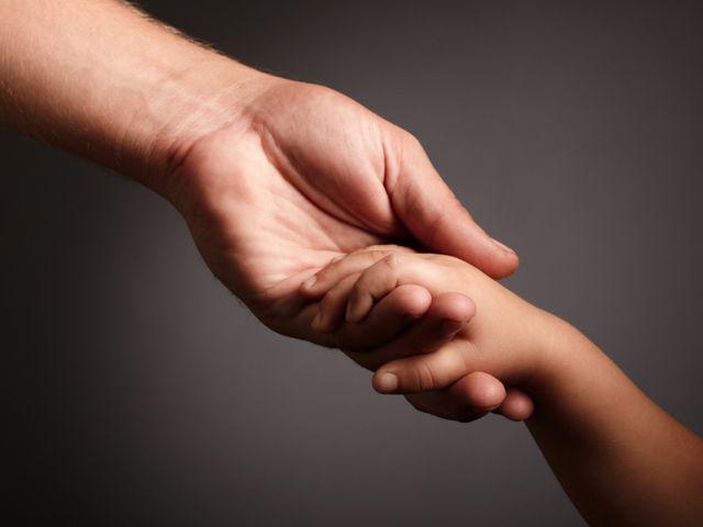 Erwachsenenhand hält Kinderhand, Foto: luxorphoto/Shutterstock.com