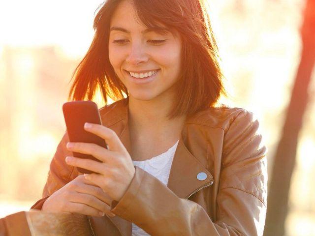 Junge Frau schaut auf ihr Smartphone, Foto: Stadtsparkasse München
