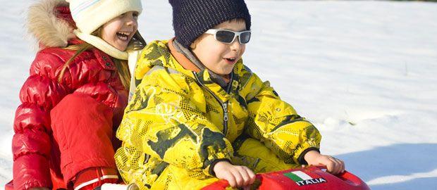 Begeisterte Kinder rodeln im Winter, Foto: Shutterstock