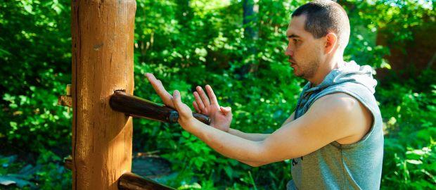 Mann trainiert Wing Tsun an Holzpfosten, Foto: Olga L. Galkina / Shutterstock.com