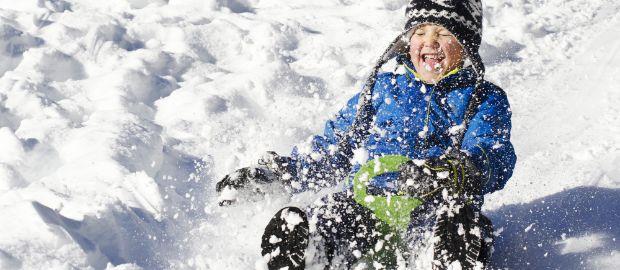 Kind rodelt und Schnee wirbelt auf, Foto: Becky Wass / Shutterstock.com