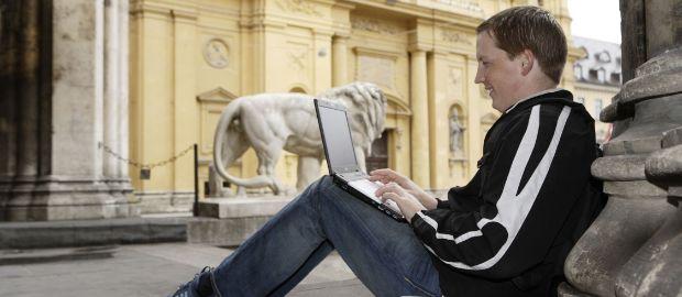M-WLAN Odeonsplatz: Junger Mann sitzt mit Laptop auf Sockel bei der Feldherrenhalle vor der Theatinerkirche, Foto: SWM
