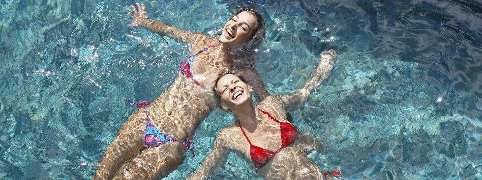 Zwei Frauen schwimmen im Hallenbad