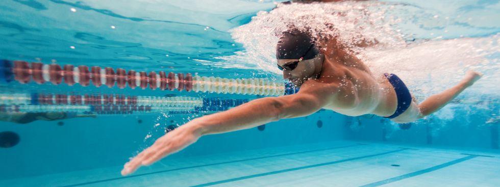 Schwimmer zieht Bahnen im Hallenbad, Foto: pio3 / Shutterstock.com