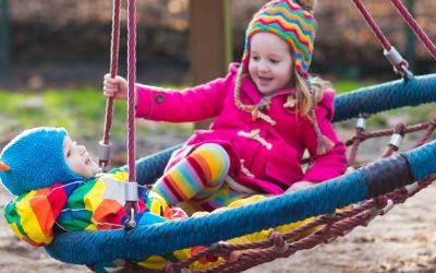 Kinder schaukeln auf Spielplatz