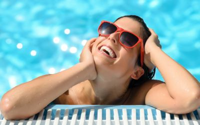 Frau mit Sonnenbrille sonnt sich am Beckenrand im Schwimmbad.