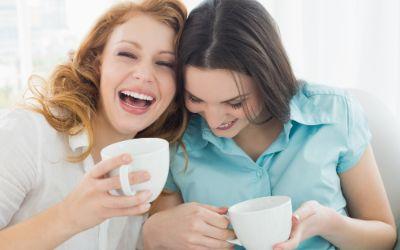 Zwei Frauen lachen mit Teetassen in der Hand