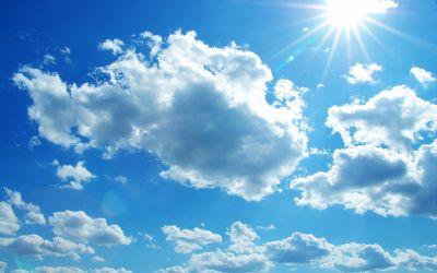 Blauer Himmel mit Sonne und Kumuluswolken