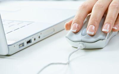 Hand auf Maus neben Laptop
