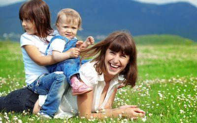 Mutter liegt auf Wiese, zwei Kinder sitzen auf ihrem Rücken