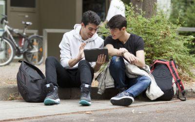 Zwei Jugendliche sitzen zusammen mit Tablet