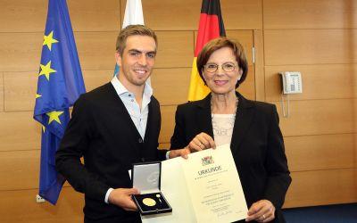 Philipp Lahm und Bayerns Sozialministerin Emilia Müller