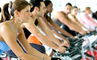 Mehrere Leute auf Fahrrädern im Fitnesscenter