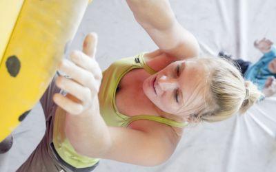 Kletterin an einer Boulderwand