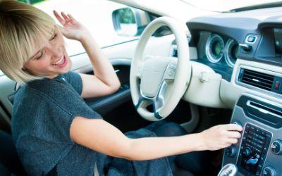 Junge Frau wechselt Radiostation im Auto