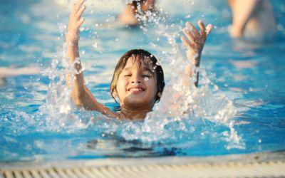 Planschender Junge im Wasser im Schwimmbad hat Spaß.