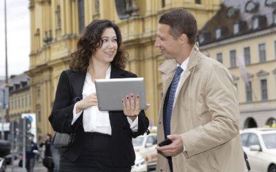 M-WLAN Odeonsplatz: Frau mit Tablet und Mann mit Smartphone vor Theatinerkirche