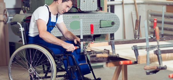 Mann im Rollstuhl arbeitet in Werkstatt