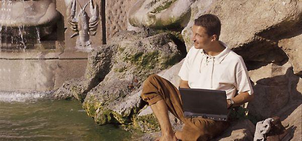 Mann mit Laptop am Brunnen im Sommer