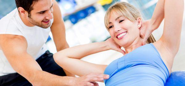 Frau macht Situps mit Personal Trainer