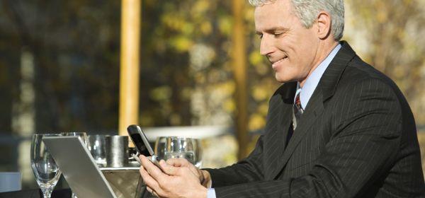 Geschäftsmann mit Laptop und Handy im Café