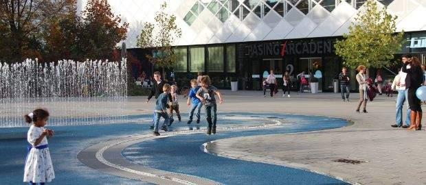 Kinder spielen am Springbrunnen vor den Pasing Arcaden