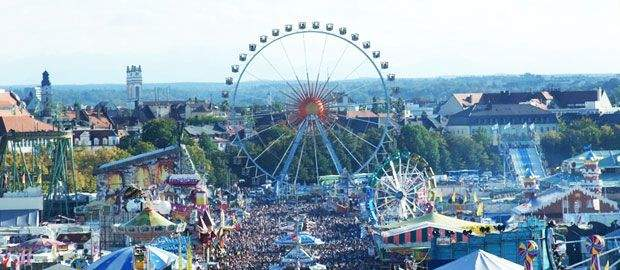 Die Wiesn von oben: Blick über das Münchner Oktoberfest mit Riesenrad und Schaustellergasse.