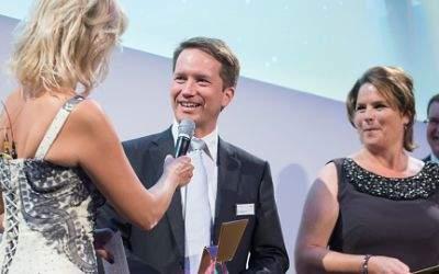 Dr. Florian Bieberbach bei der Preisverleihung in Berlin im Gespräch mit Moderatorin Carola Ferstl. Rechts die Laudatoren Marion Schulte und Jens Raschke.