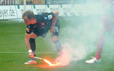 Stefan Aigner trägt brennende Pyrotechnik vom Rasen.