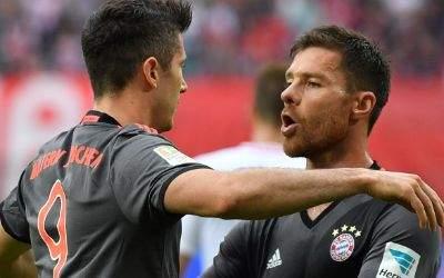 Robert Lewandowski (l.) und Xabi Alonso vom FC Bayern München jubeln.