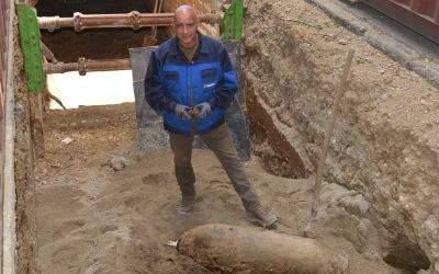 Sprengmeister Flakowski mit dem entfernten Zünder vor der frei gelegten Bombe
