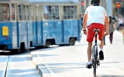 Radfahrer fährt hinter Straßenbahn her.