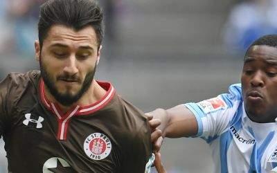 Enver Cenk Sahin (l) von St. Pauli und Romuald Lacazette von München kämpfen um den Ball.