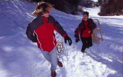 Zwei Personen rennen einen schneebedeckten Hang hinauf.